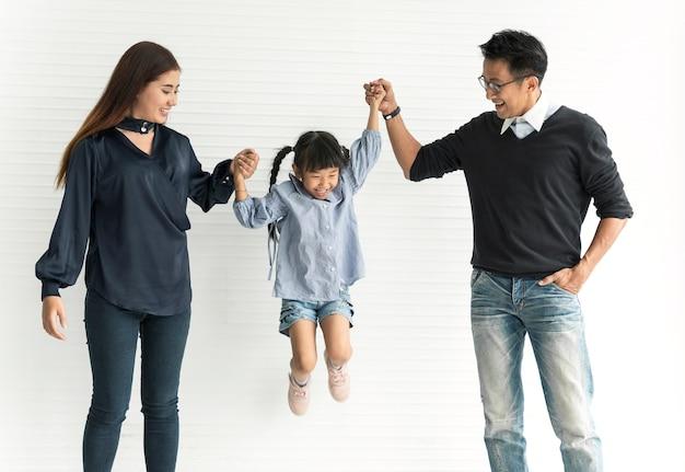 Mãe asiática e pai da família com a filha feliz junto na sala de visitas em casa.