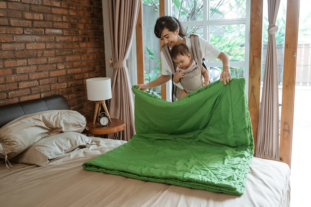 Mãe asiática e seu bebê limpando e arrumando o cobertor na cama