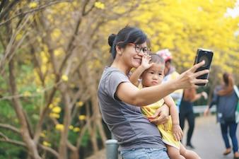 Mãe asiática e seu filho no parque com flor de trombeta amarela