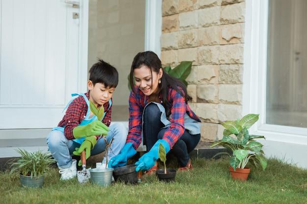 Mãe asiática e seu filho plantar uma planta em casa jardim