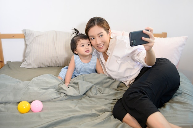 Mãe asiática e sua filha bebê estão fazendo selfie ou videochamada para o pai na cama.
