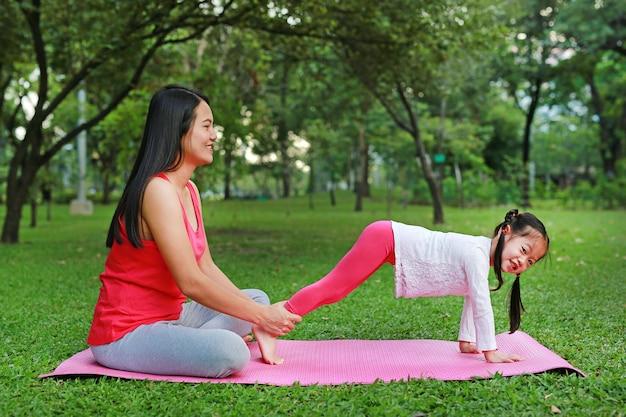 Mãe asiática e sua filha que fazem o exercício no parque público.
