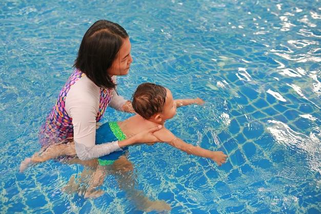 Mãe asiática, ensinando o bebê na piscina