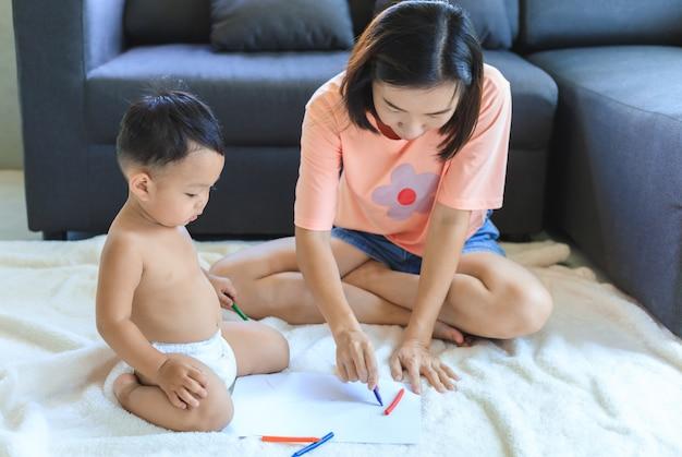 Mãe asiática ensinando seu bebê desenhar