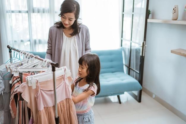 Mãe asiática fazendo compras com a filha em uma butique de roupas