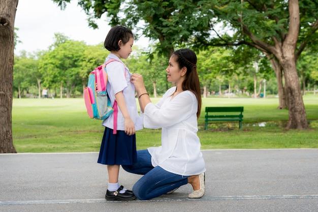 Mãe asiática feliz com o estudante dos miúdos na escola.