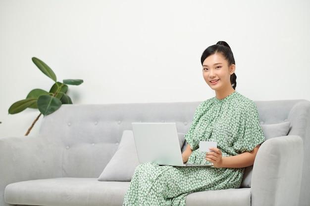 Mãe asiática grávida pedindo roupas para o bebê, usando laptop e cartão de crédito em casa