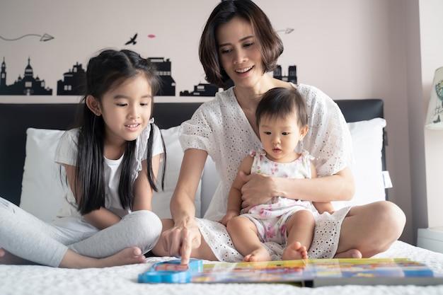 Mãe asiática, lendo o livro de música para suas filhas, sentado na cama.