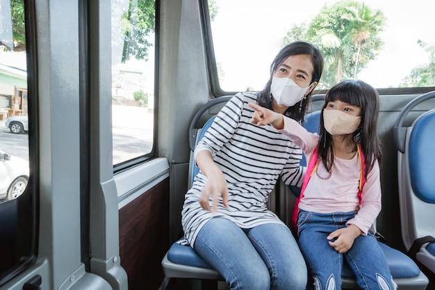 Mãe asiática levando a filha para a escola no ônibus de transporte público usando máscara no rosto