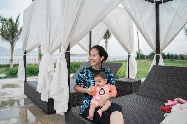 Mãe asiática mantém o bebê sentado no colo enquanto está sentado