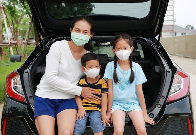 Mãe asiática, menino e menina usam máscara facial de higiene, sentados em um carro hatchback olhando pela câmera durante o surto de coronavírus (covid-19)