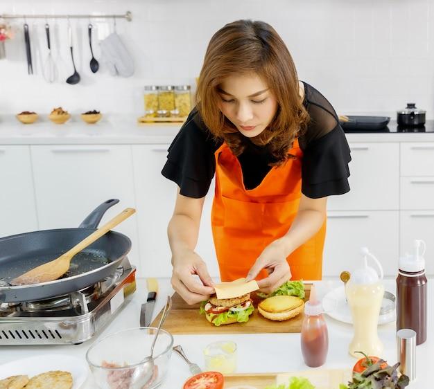 Mãe asiática moderna bonita no avental de cozinha laranja cuidadosamente coloque manteiga no hambúrguer em casa como um adorável café da manhã para criança e família amada.