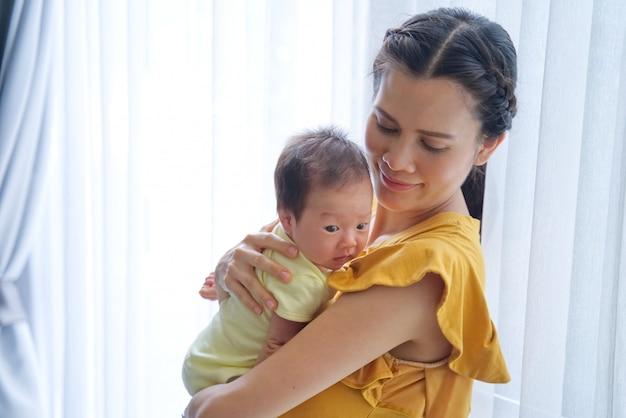 Mãe asiática que guarda seu bebê em seu braço e que olha a com sorriso.