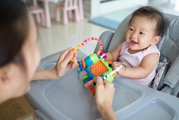 Mãe asiática que joga o brinquedo com seu bebê que senta-se na cadeira dinning em casa.