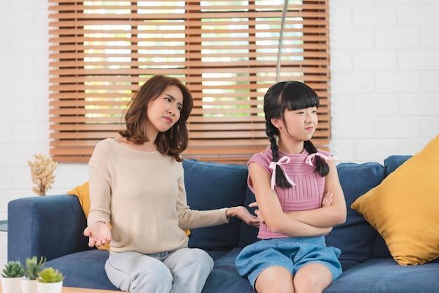 Mãe asiática são filhas brigando em casa. conceito de relacionamento familiar