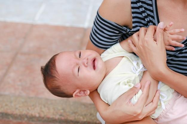 Mãe asiática, segurando, gritando, bebê recém-nascido, menino