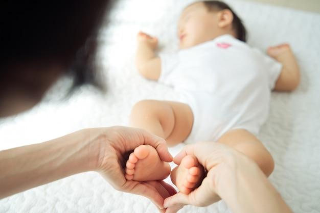 Mãe asiática, segurando os pés do bebê em forma de coração, enquanto a criança está dormindo