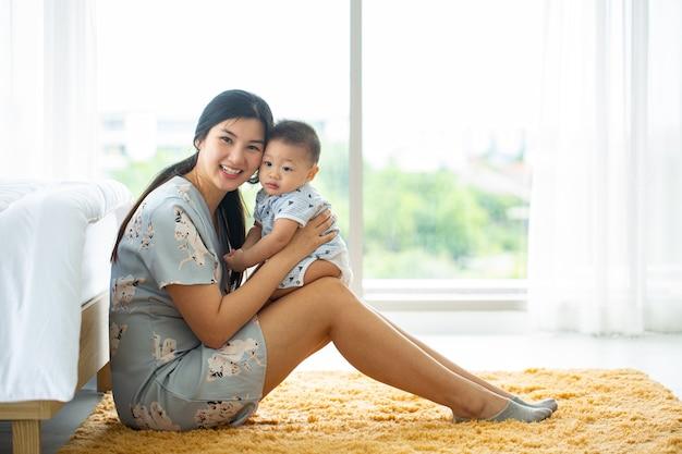Mãe asiática segurando seu bebê ao lado do quarto.