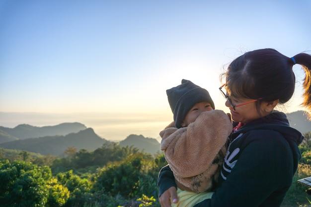Mãe asiática segurando seu filho de 1 ano e um mês