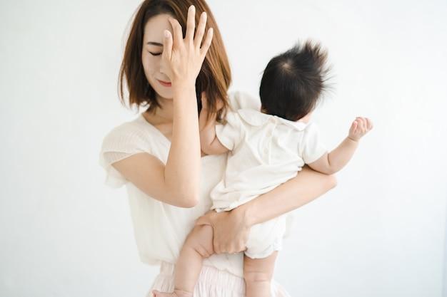 Mãe asiática segurando um bebê e parecendo cansada