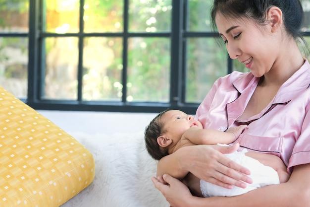 Mãe asiática, segurando uma criança de 1,5 meses