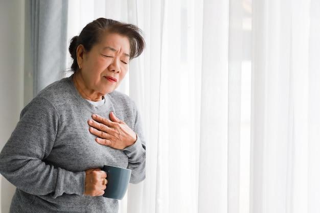Mãe asiática sênior mulher doente com coração attact na sala de estar