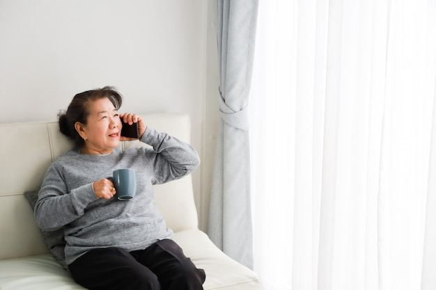 Mãe asiática sênior mulher falando com telefone celular e tomando café na sala de estar