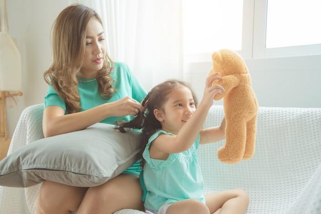 Mãe asiática trança de cabelo para sua filha antes de ir para a escola