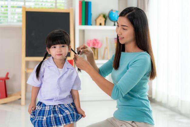 Mãe asiática trança o cabelo das filhas
