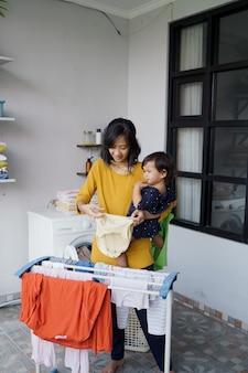 Mãe asiática, uma dona de casa secando e pendurando roupas na lavanderia de casa enquanto carrega seu bebê