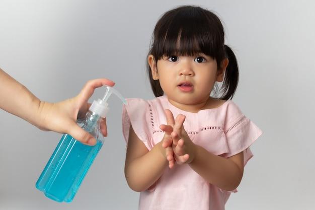 Mãe asiática usando gel anti-séptico de álcool para limpar as mãos do bebê. desinfecção por coronavírus