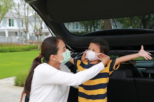 Mãe asiática usando máscara protetora para o bebê antes de viajar durante o surto de coronavírus e gripe