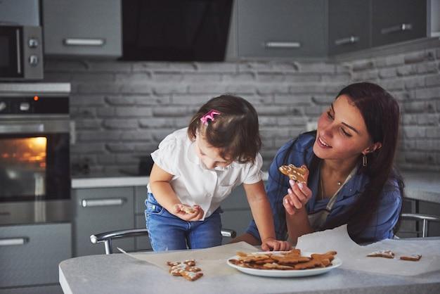 Mãe assar com a filha na cozinha.