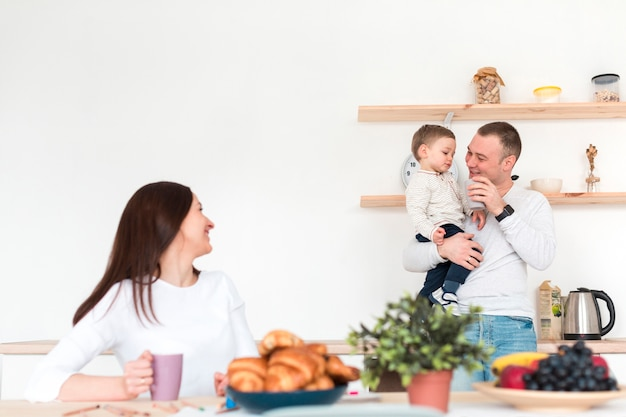 Mãe assistindo pai segurando criança na cozinha