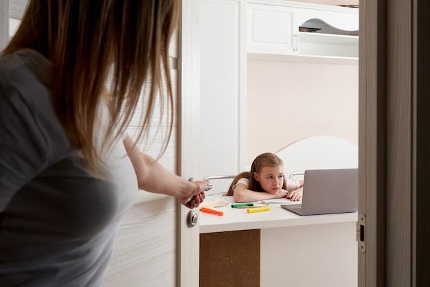 Mãe assistindo sua filha triste fazendo lição de casa no laptop em casa