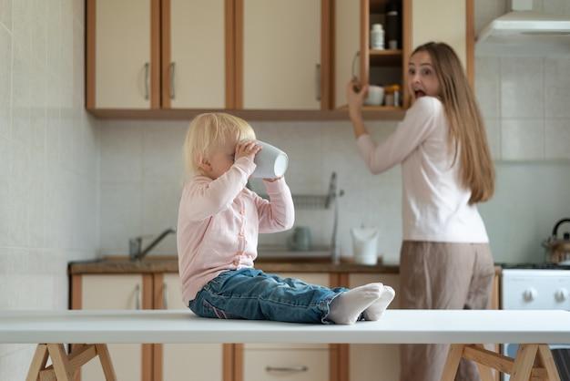 Mãe assustada e criança com caneca nas mãos na cozinha. criança sem supervisão.