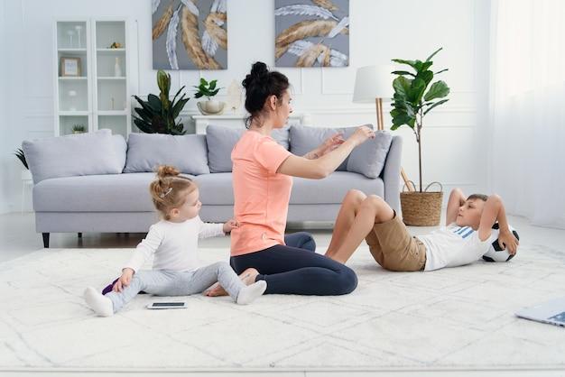 Mãe atlética com filho fazendo exercícios matinais em casa enquanto o bebê brinca