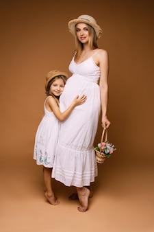 Mãe atraente de corpo inteiro com uma cesta de flores e a filha abraçando a barriga de grávida com vestidos brancos de verão e chapéus abaulados. isolado.