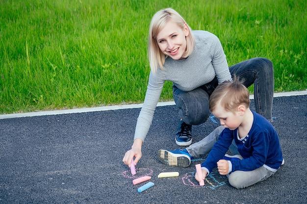 Mãe atraente (pessoa do sexo feminino) e menino pintado com giz de cera colorido no asfalto do parque em um fundo de grama verde
