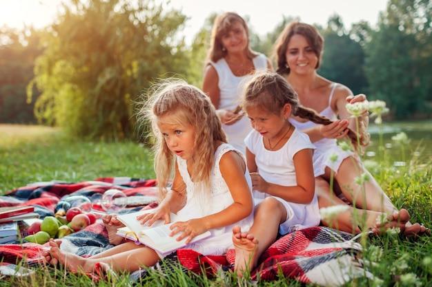 Mãe, avó e filhos tecendo tranças uns aos outros, família se divertindo durante um piquenique no parque,