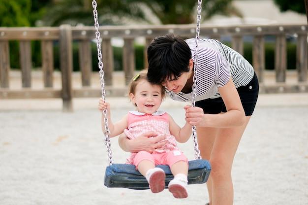 Mãe, balançando, dela, filha pequena, ligado, um, balanço, em, um, pátio recreio