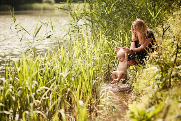 Mãe banha seu filho pequeno em um rio entre grama verde alta