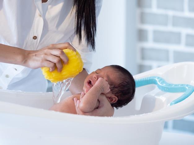 Mãe banho menino asiático bebê recém-nascido na banheira