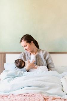 Mãe, bebê segurando, em, braços cama