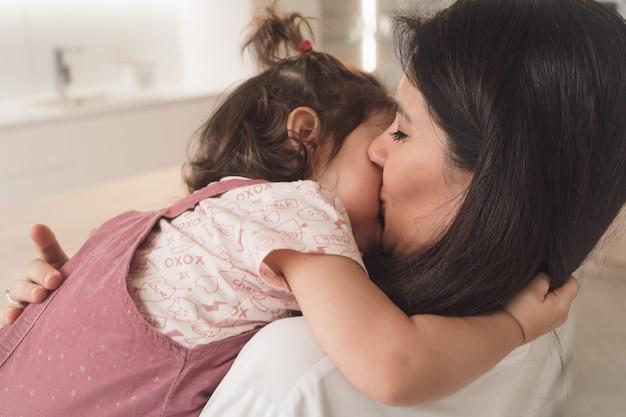 Mãe beija a filha dela. filha e mãe abraçam gentilmente.