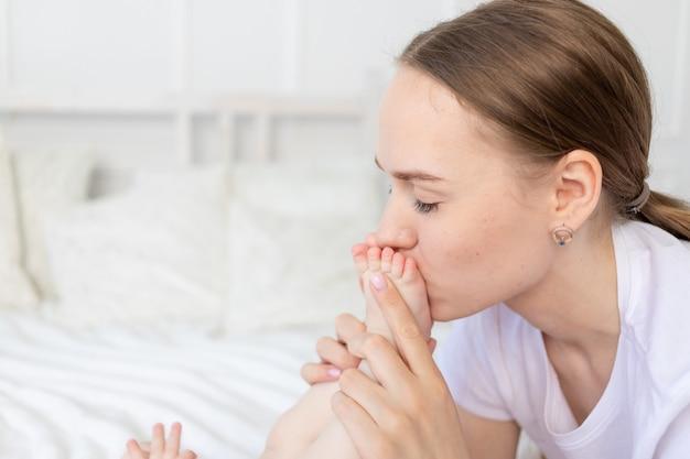 Mãe beija os pés do bebê e cheira na cama em casa, feliz maternidade