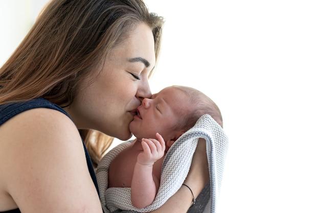 Mãe beija seu espaço de cópia sorridente bebê recém-nascido.