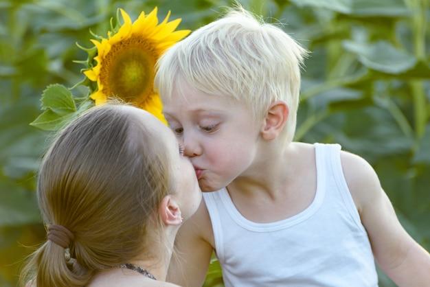 Mãe beija seu filho pequeno, girassóis florescendo