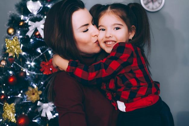 Mãe beija uma filha pequena na árvore de natal