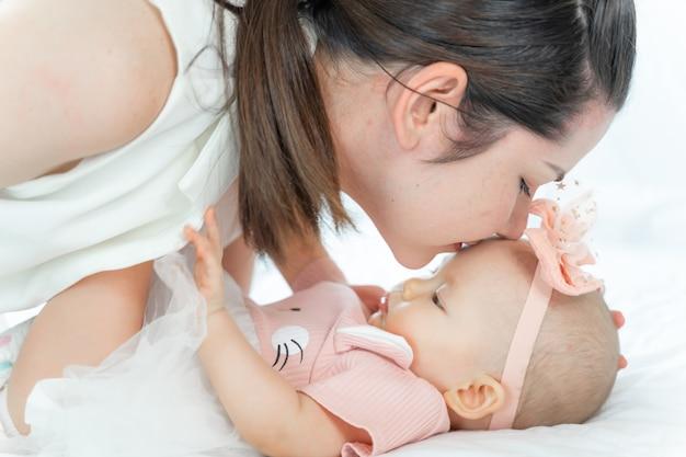Mãe beijando a cabeça de seu bebê dormindo